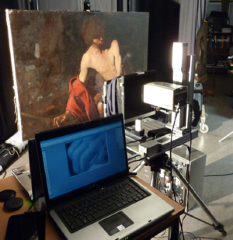 A laptop in front of a painting.