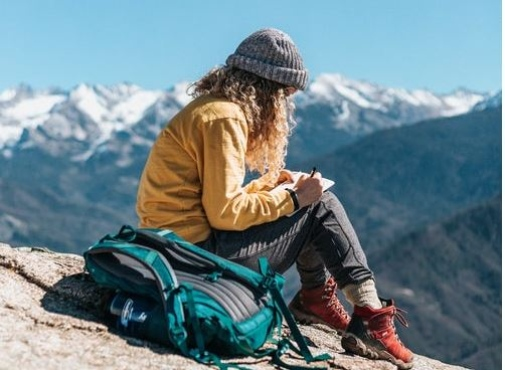 Girl sitting on a mountain reading a book. Photo by Tyler Nix on Unsplash