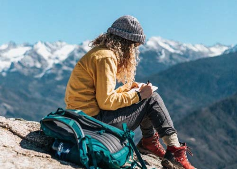Student taking notes in the mountains