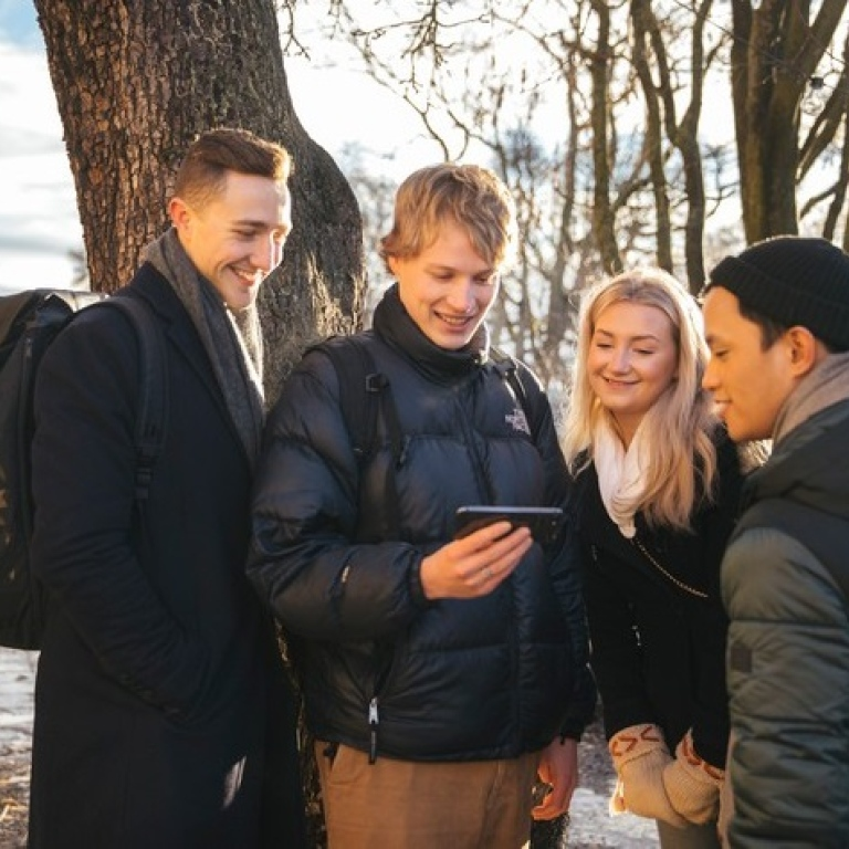 Students outdoors looking at a mobile Photo: Niklas Björling