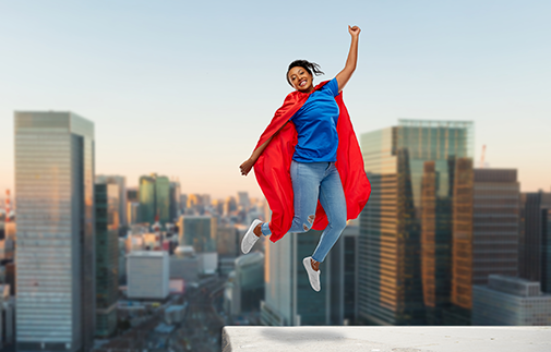 Woman dressed in super hero cape on the rooftop with a city skyline in the background.
