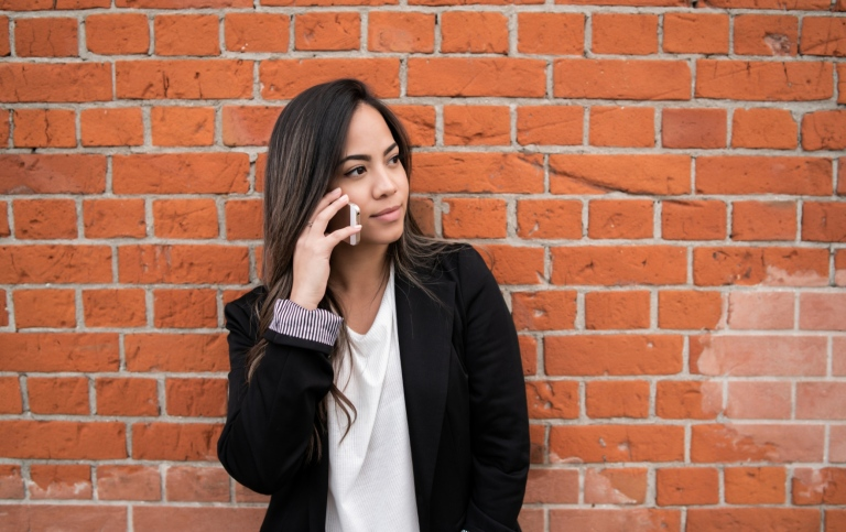 Woman with mobile phone by a red brick wall. Photo: Mostphotos