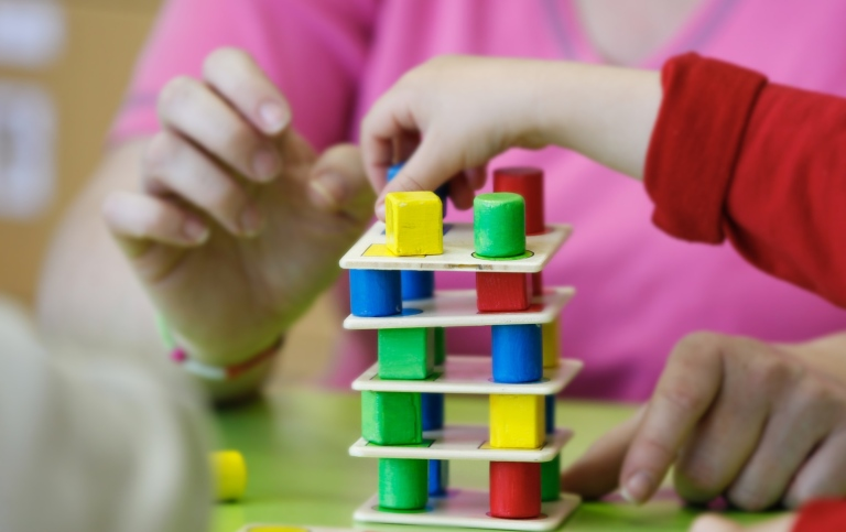 Children constructing a tower with small blocks and plates.