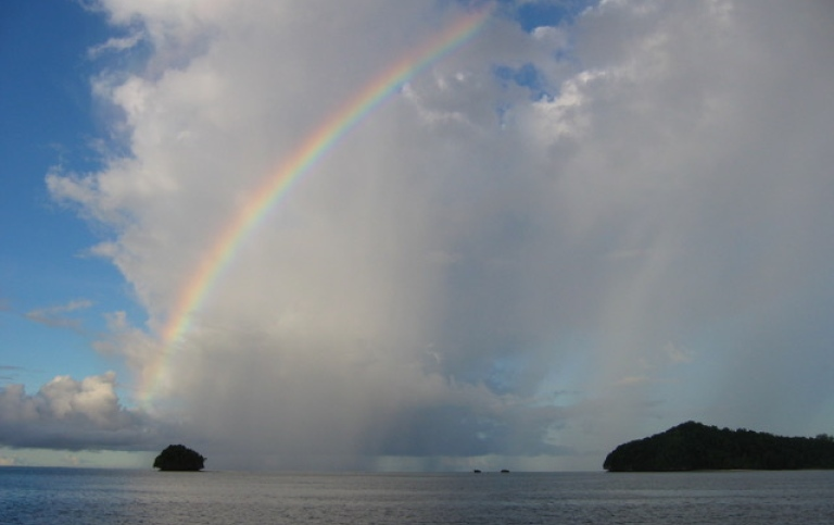 cloudy sky with a rainbow and two islands on the horizont
