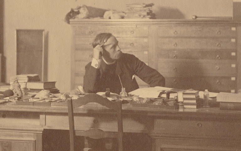 Norwegian geologist, Waldemar Christofer Brögger, sitting at his desk, 1881.