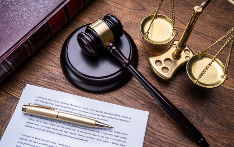 Wooden Gavel Golden Scale And Law Book On Table