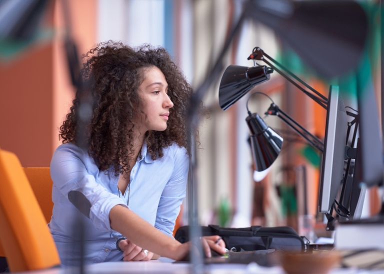 Young woman at an office desk. Photo: Mostphotos