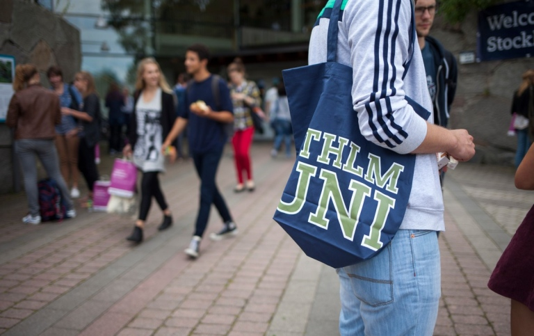 student at Stockholm University on the background, focus on a STHLM UNI bag on the right side