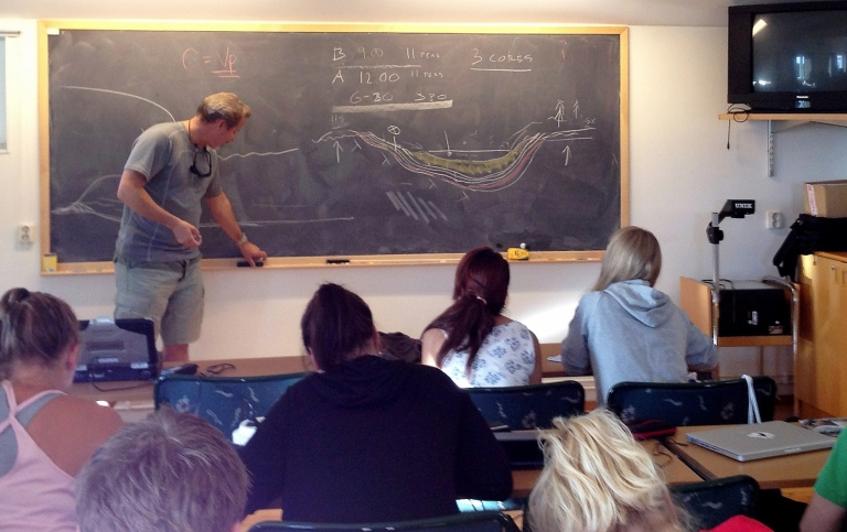 Teacher by the black board in front of a class of students