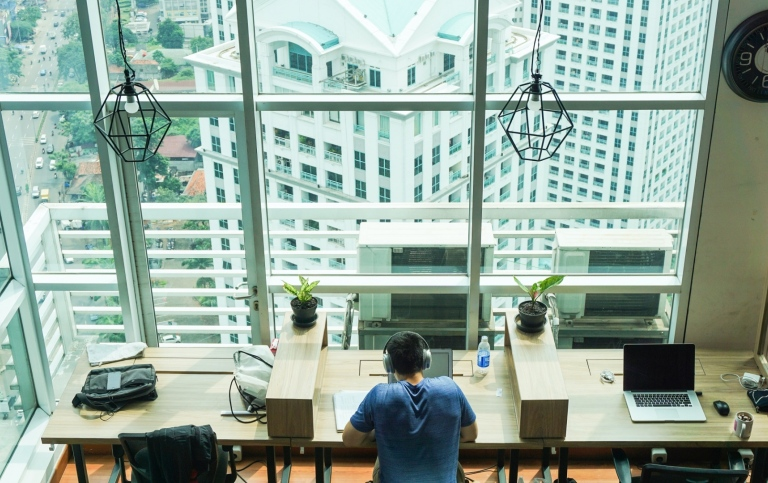 Young man with a computer in a skyscraper in Jakarta. Photo: Al Ghazali/Unsplash