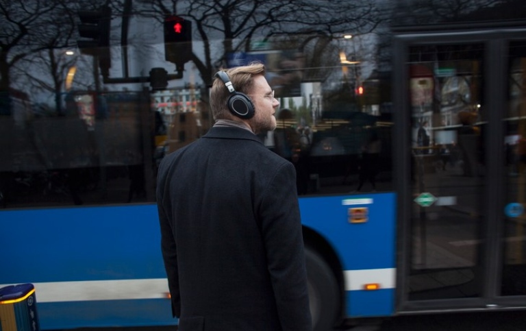 A man with earphones next to a bus. Photo: Jens Olof Lasthein