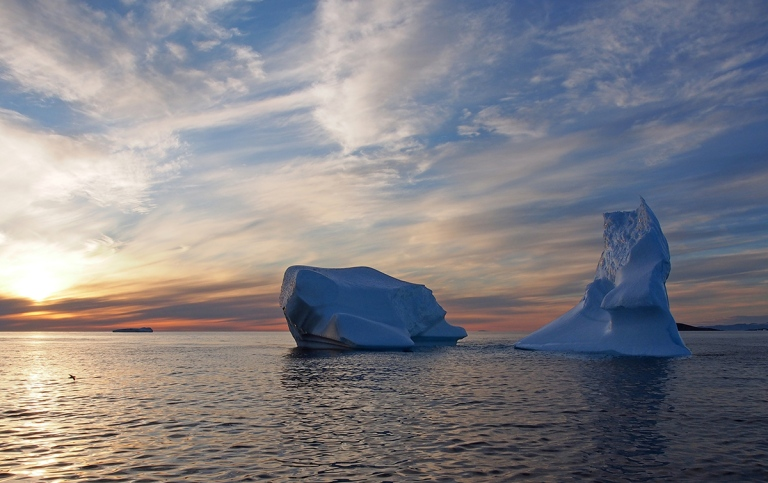 two smaller icebergs, greenland, with sunset on the left side