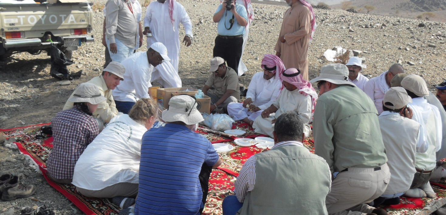 people sitting on a big matt on the deserts, eating lunch