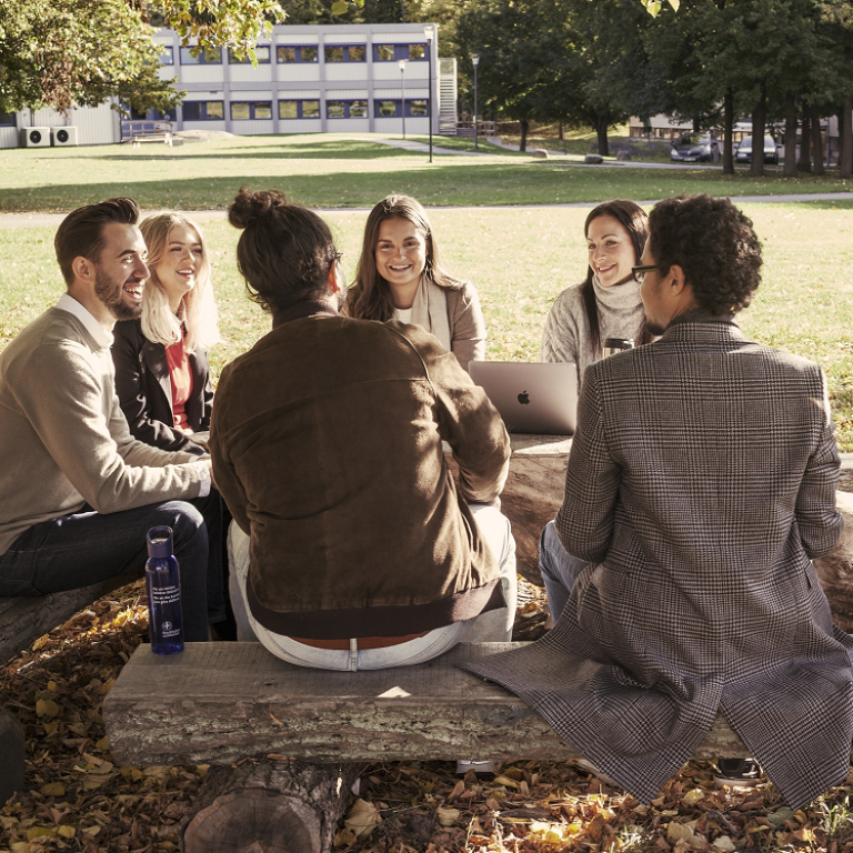 Seven students in conversation on benches on a lawn, with laptop. Photo: Jens Olof Lasthein