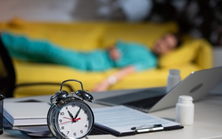 Alarm clock with a blurred person lying in a sofa in the background. Foto: LightField/Mostphotos