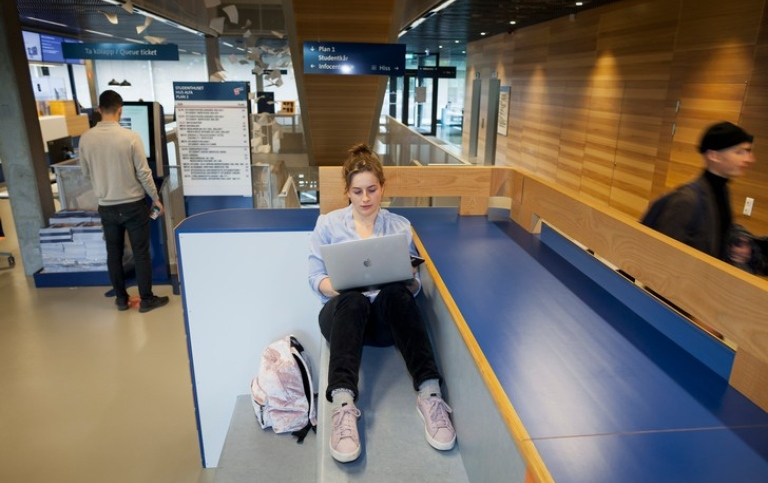 A female student is studying with a laptop in Studenthuset.