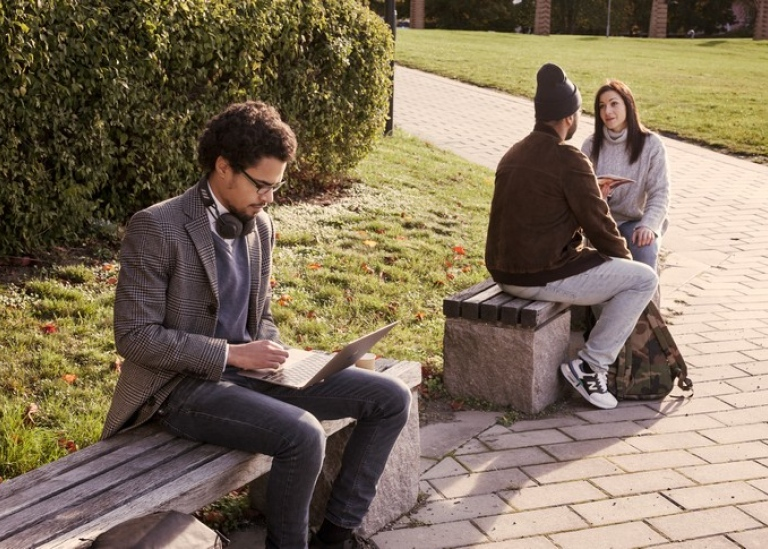 Three students on campus, one has a laptop.