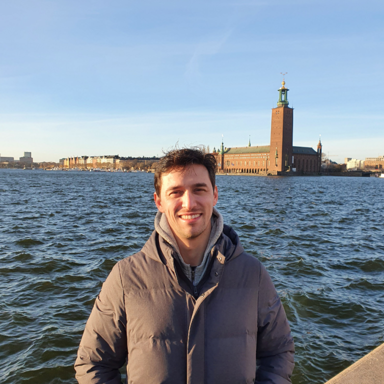 A photo of Guilherme Tácito de Luna in front of lake Mälaren and the Stockholm City Hall